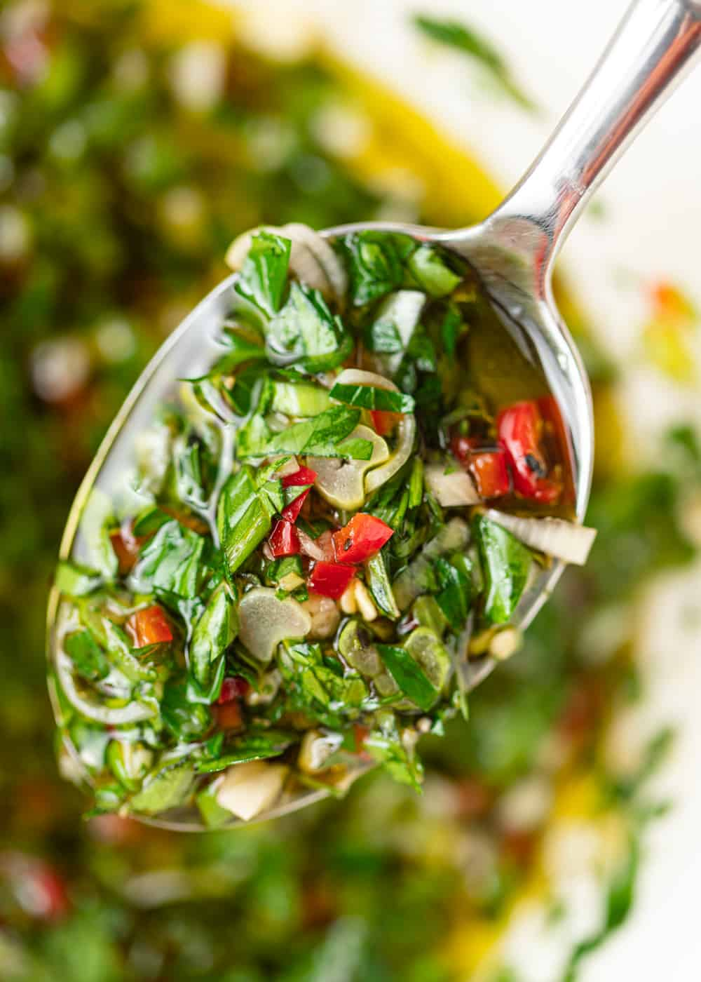 spoon with chopped garlic, red chile pepper and herbs in oil