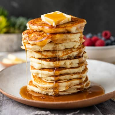 pancakes dripping in maple syrup and butter on top