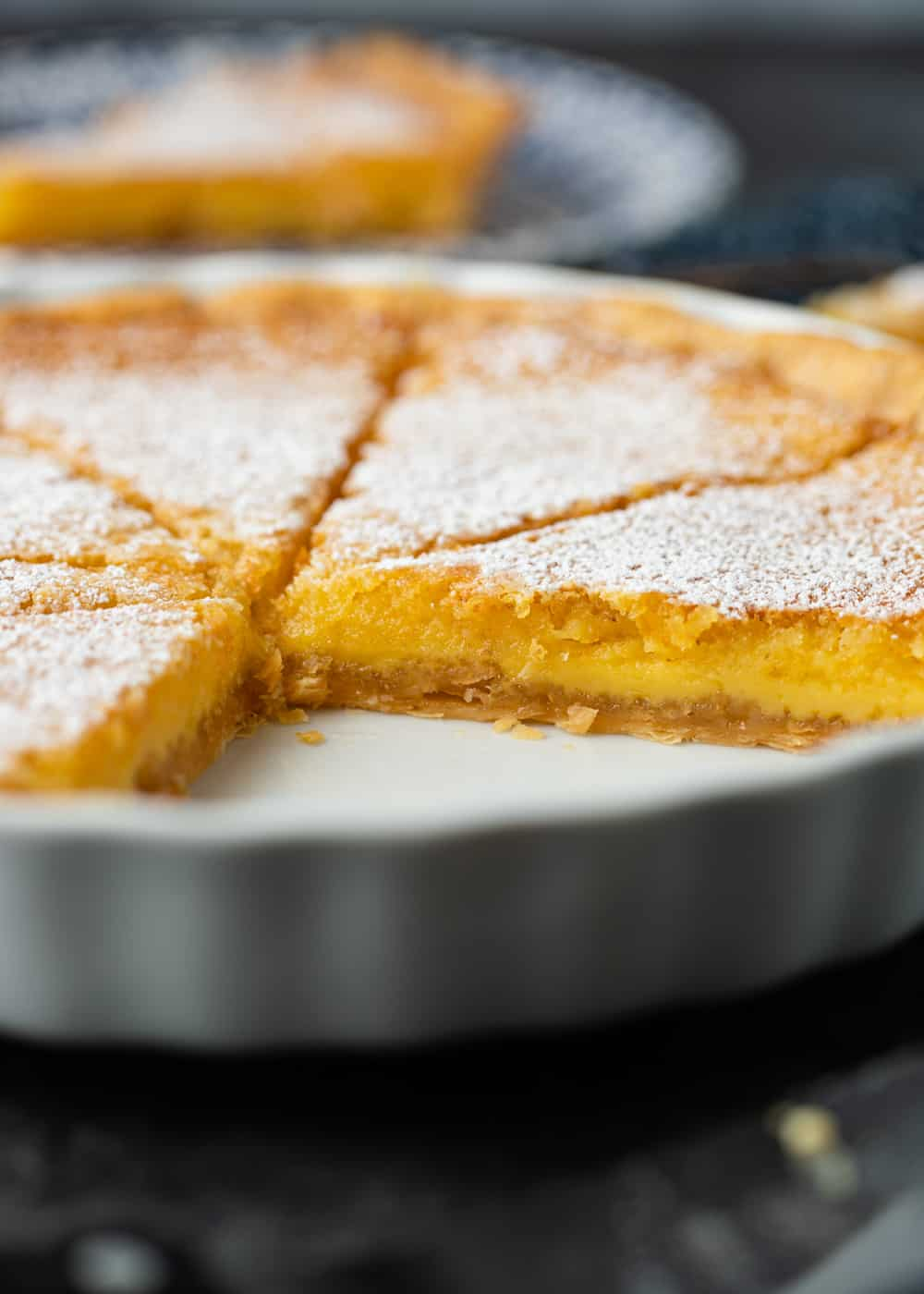 sliced lemon tart in white pan