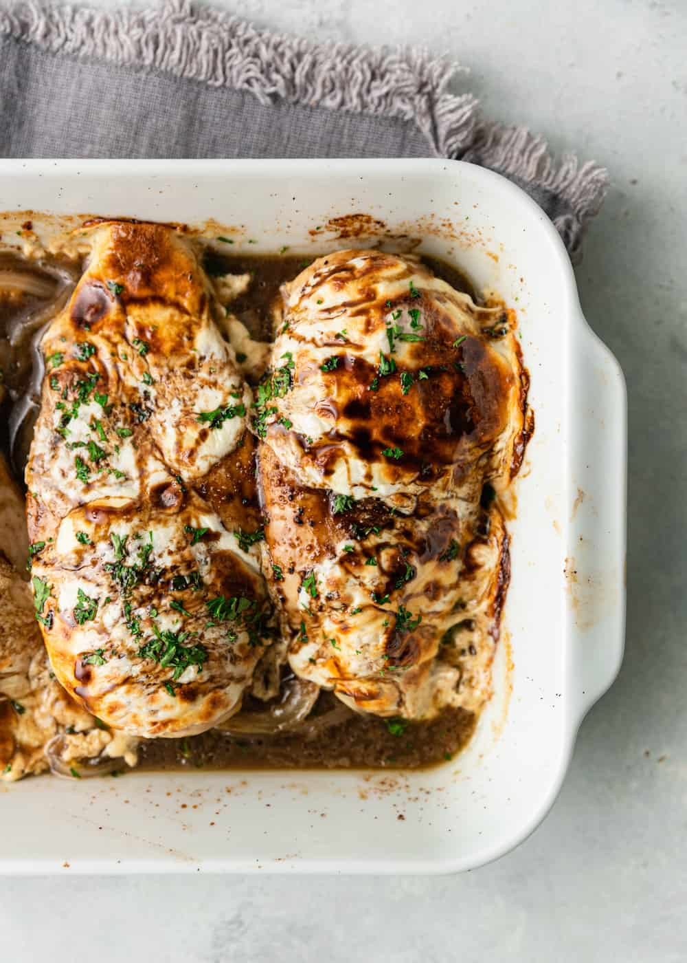 overhead photo of baked honey balsamic chicken in white casserole dish
