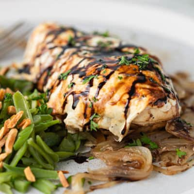 close up of honey balsamic baked chicken breast on bed of onions and green beans