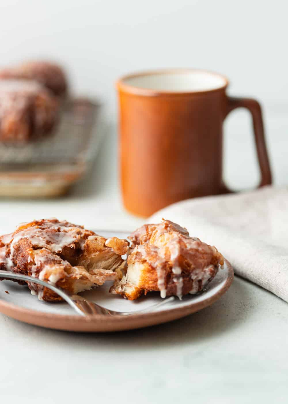 apple fritter on a plate with a cup of coffee