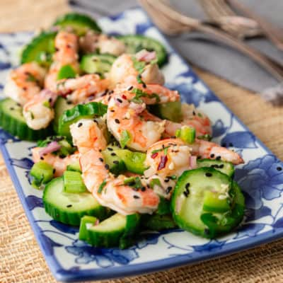 A close up of a plate of Shrimp Cucumber and Salad on blue and white tray