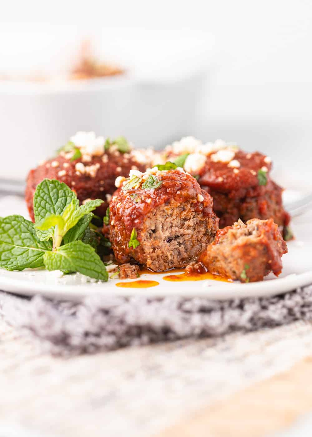 cut side of meatball with tomato sauce and mint leaves on white plate