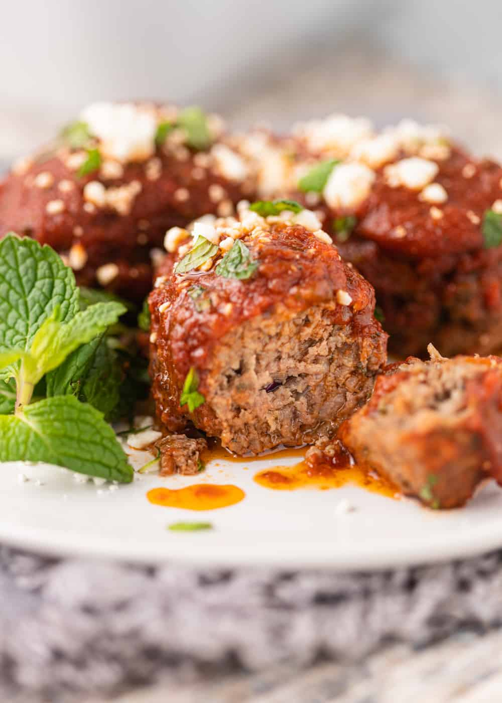 close up of Greek Meatballs in Tomato Sauce on white plate with one meatball cut open