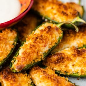 A close up of a plate of stuffed jalapeños with crunchy breadcrumbs on top