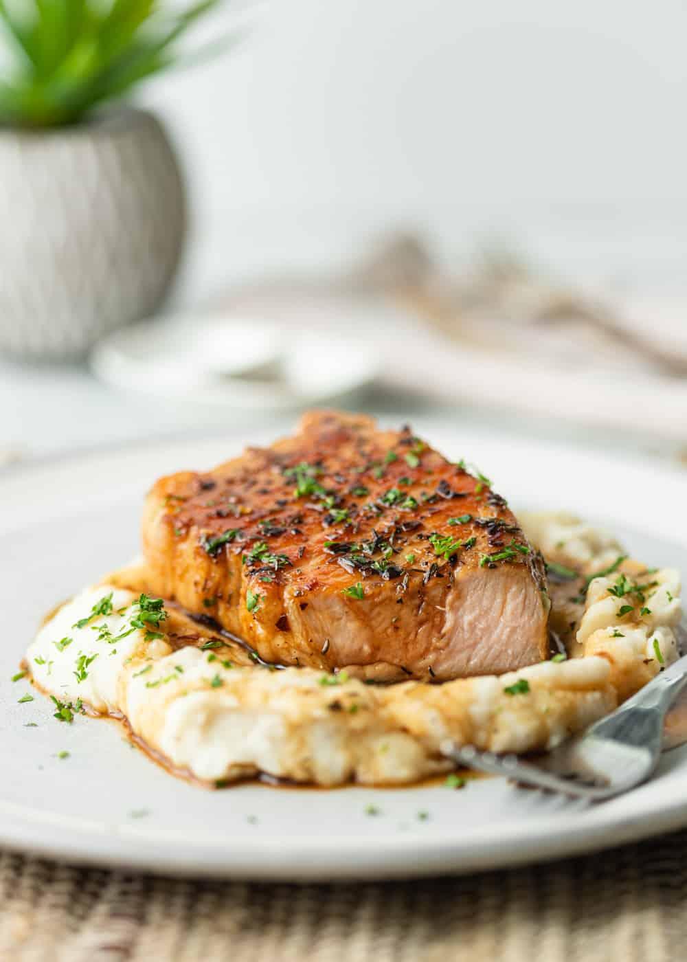 plated pork chop on masehed potatoes with glaze sauce