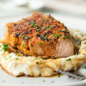 A close up of a plate of Glazed Pork on mashed potatoes