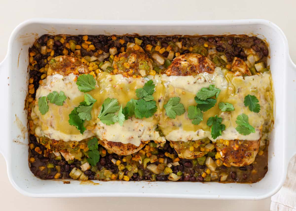 baked boneless chicken breasts in casserole dish covered with black beans, corn, and cheese