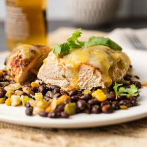 A close up of a plate of food on a table, with Chicken breast on black beans