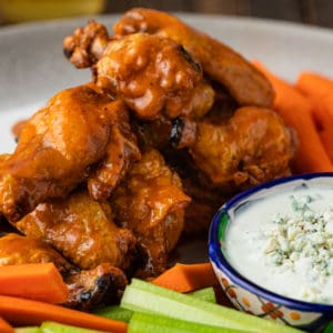 A close up of a plate of crispy baked Chicken wings with buffalo sauce