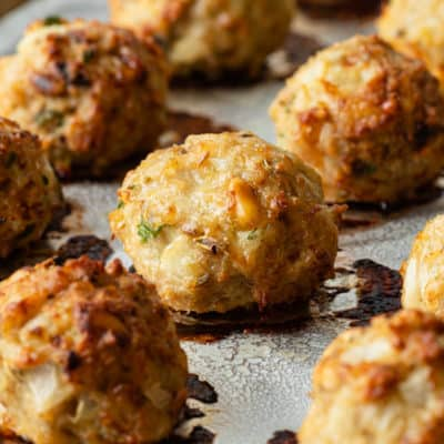 close up of a baked chicken meatballs on sheet pan