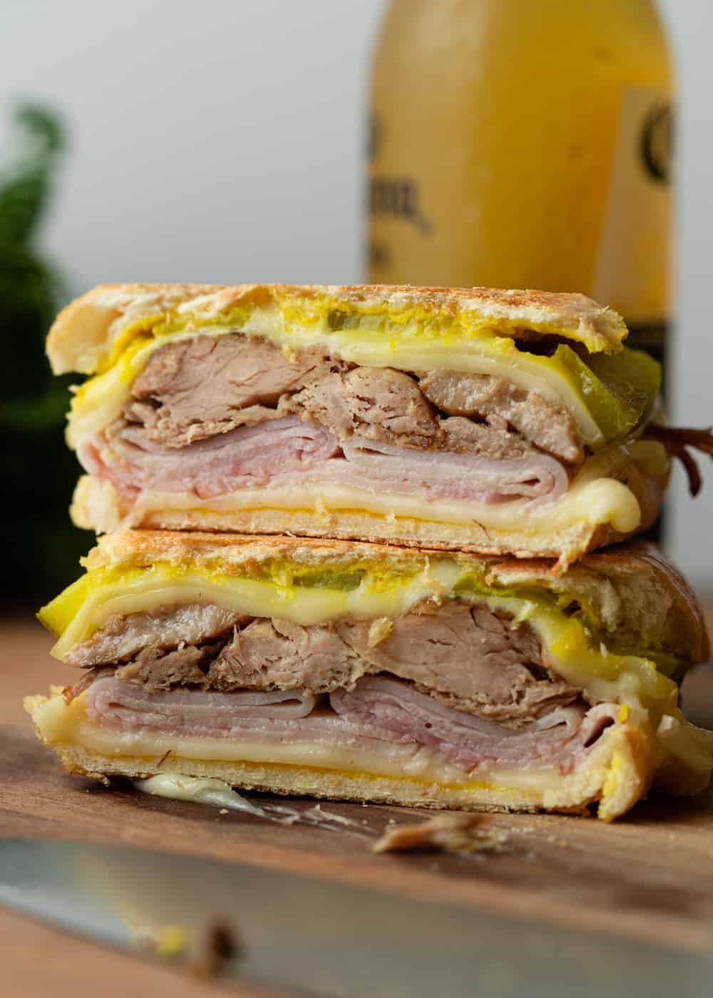Close up image of sandwich Cubano with pork, Swiss cheese, mustard, ham and pickles.
