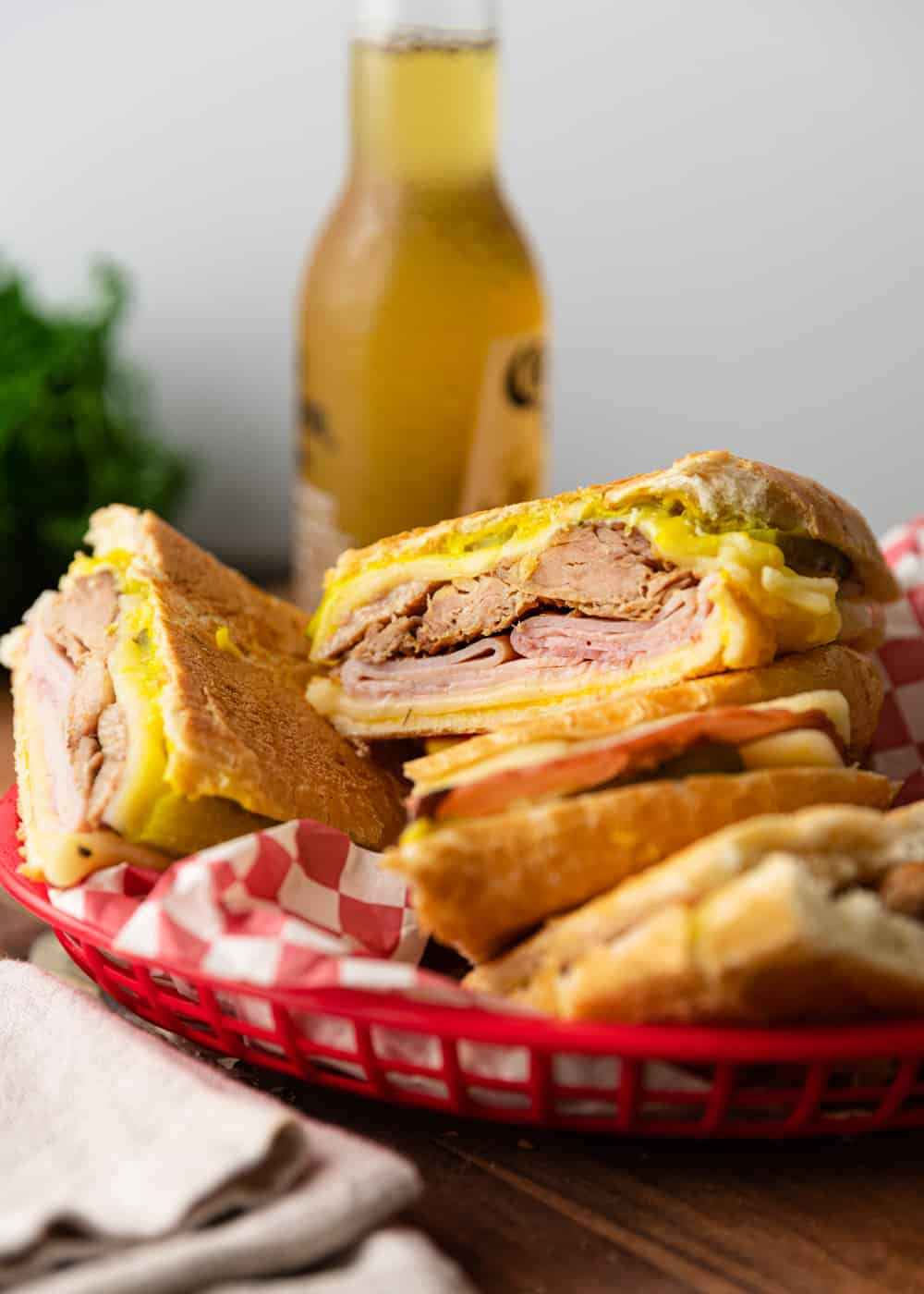 Sliced Cuban sandwiches in a basket with beer in the background.