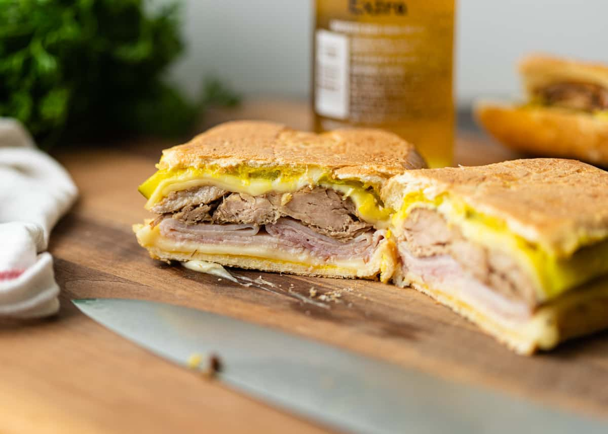 Visible layers in Cuban sandwich on a wooden cutting board, with a knife visible.