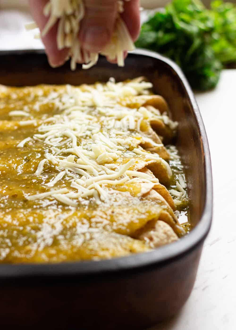 sprinkling Mexican cheese onto enchiladas in casserole dish