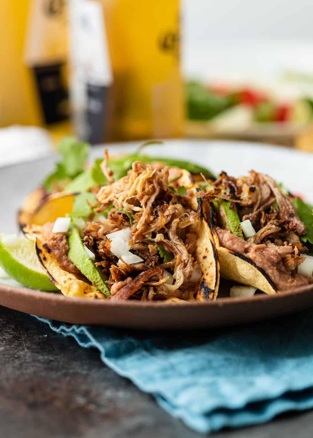 teo carnitas tacos on a plate with onion cilantro avocado