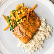 A plate of food with rice grilled salmon and vegetables