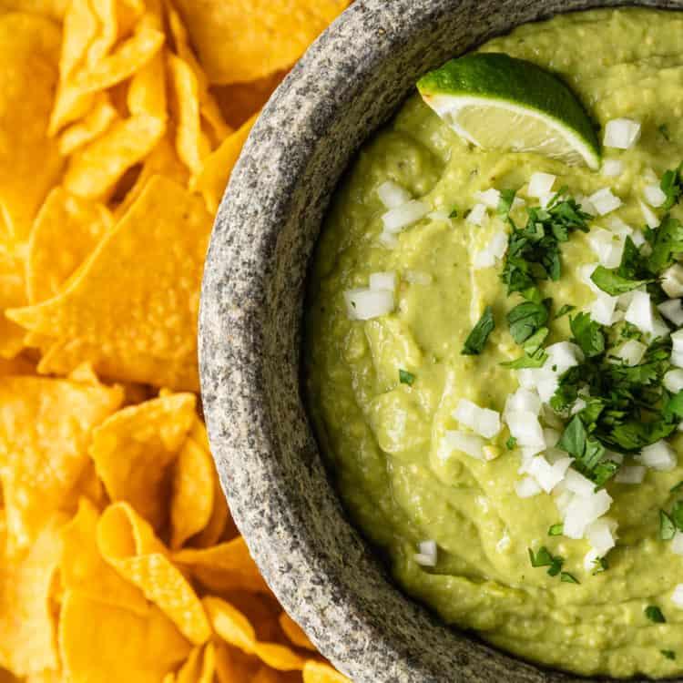 bowl of guacamole salsa and tortilla chips