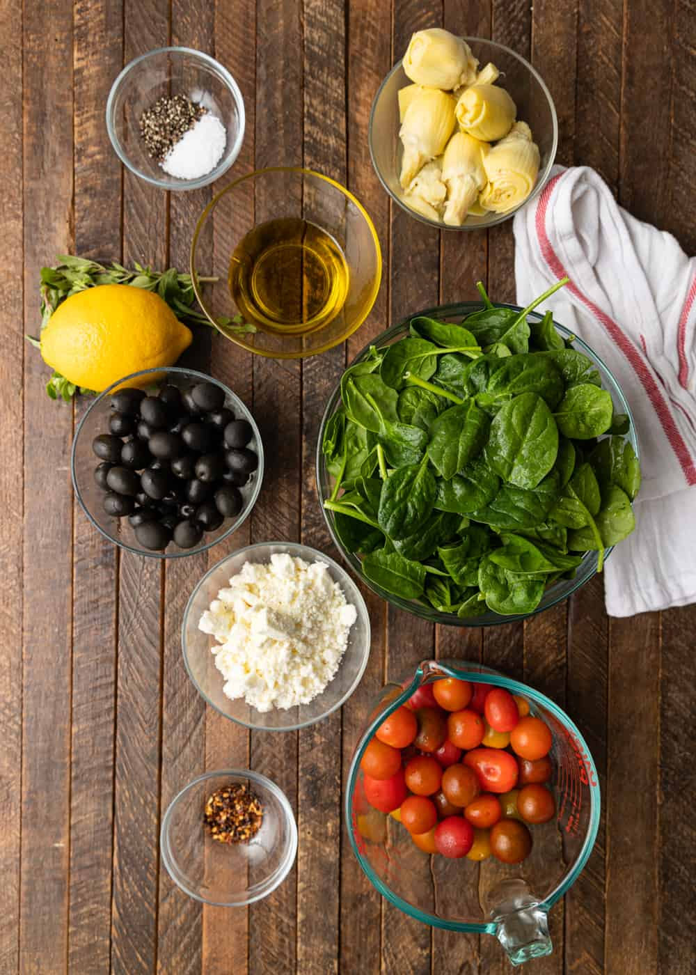 ingredients in pep bowls to make chicken dinner - black olives, tomatoes, feta cheese, spinach, and artichokes