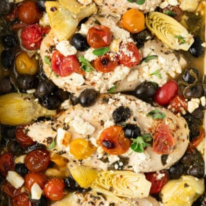 overhead photo of tomatoes on chicken breasts and artichoke hearts, olives