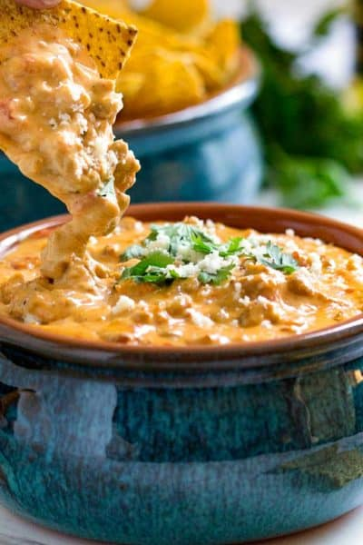 dipping tortilla chips into queso dip made from scratch in a blue crock