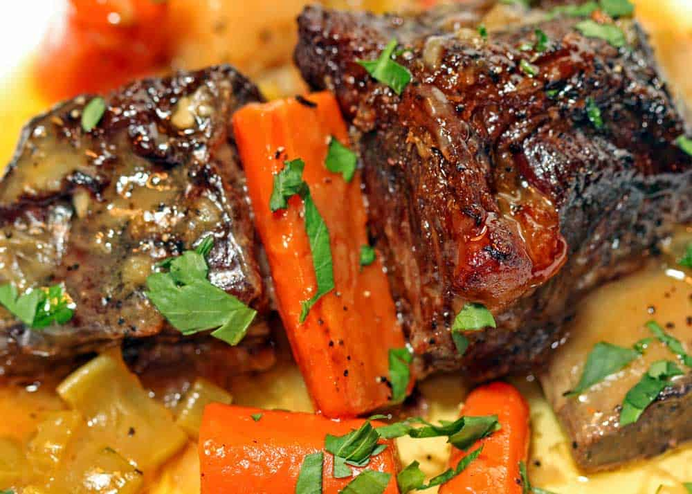 a close up look at braised beef short ribs and carrots