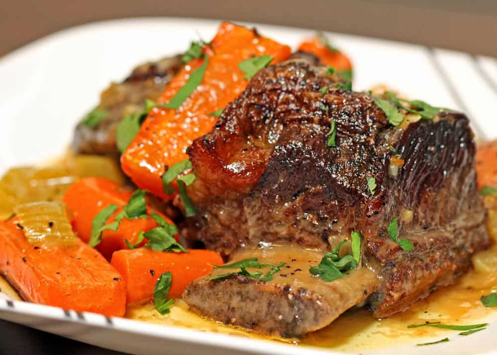 braised beef short ribs and carrots on a white dish
