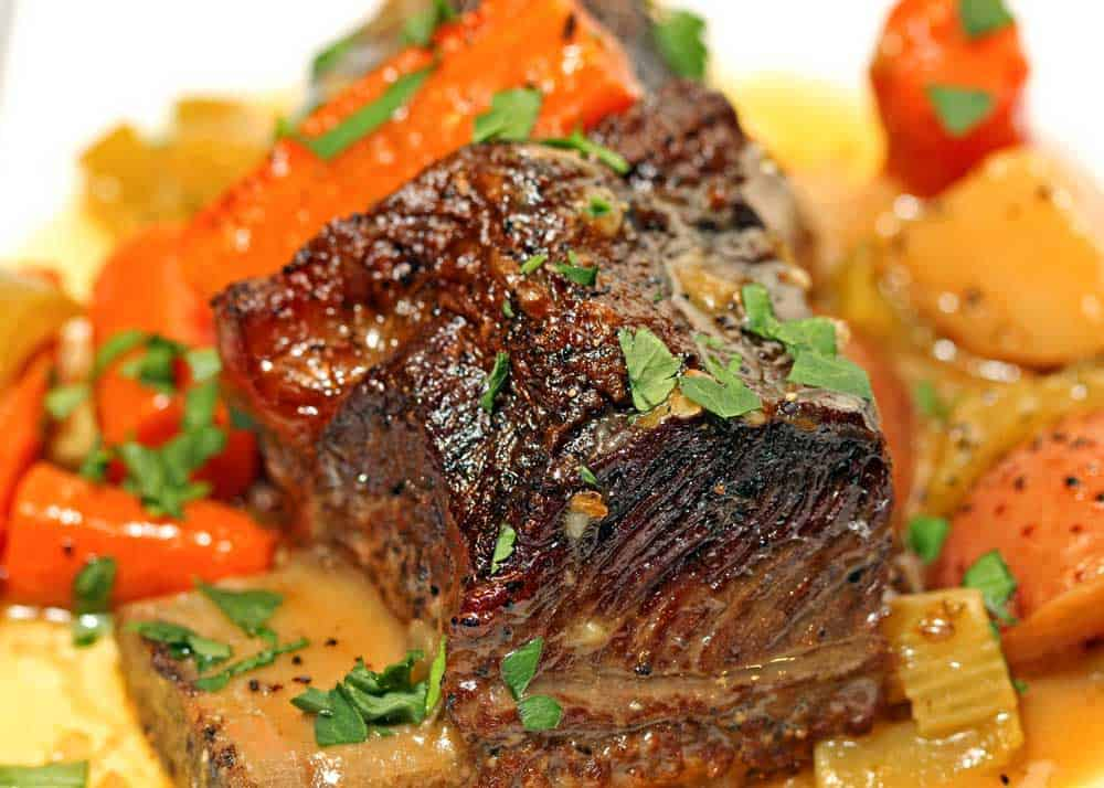 close up of braised beef short ribs, carrots and potatoes on a white dish