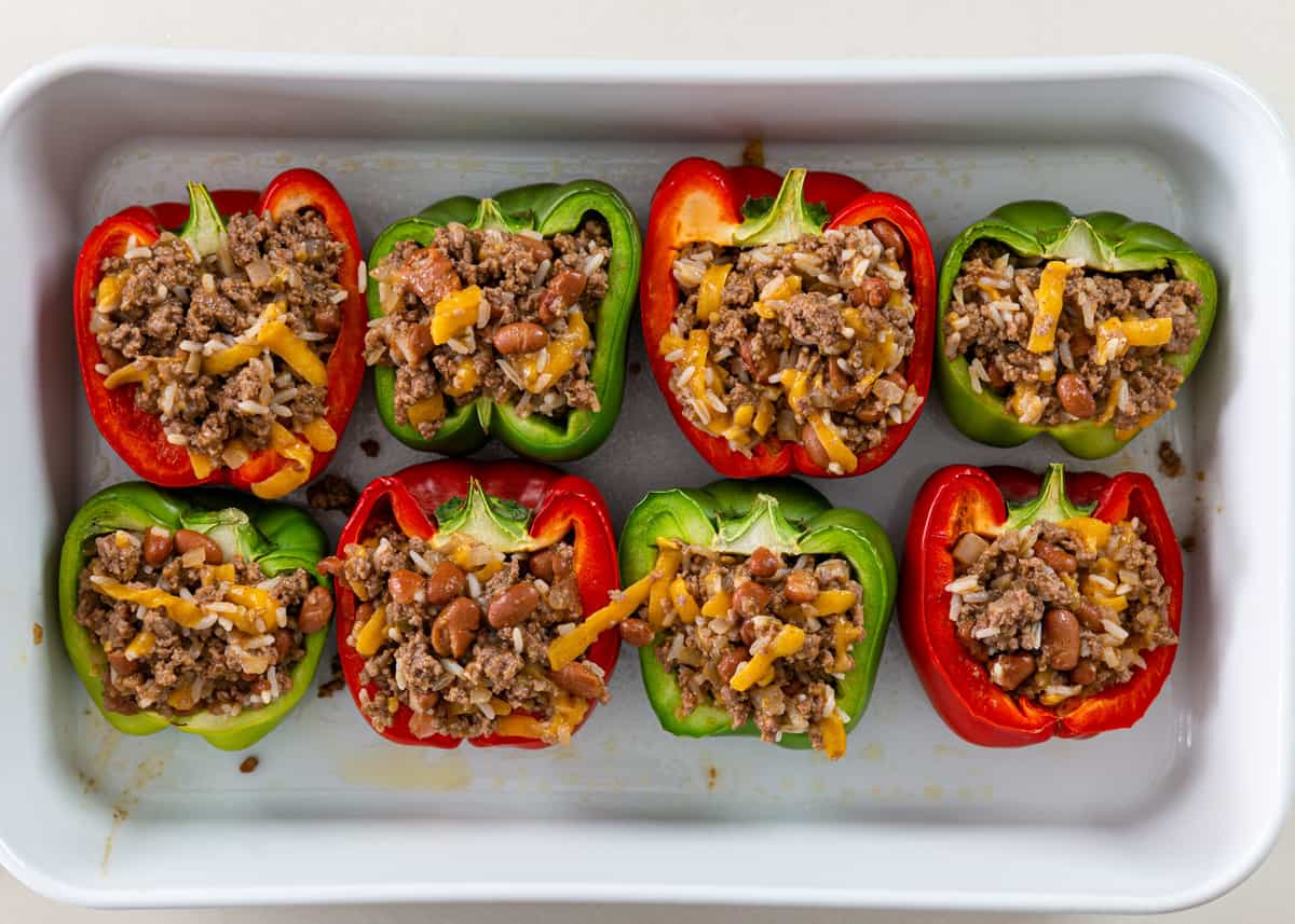 green and red taco stuffed peppers in casserole dish