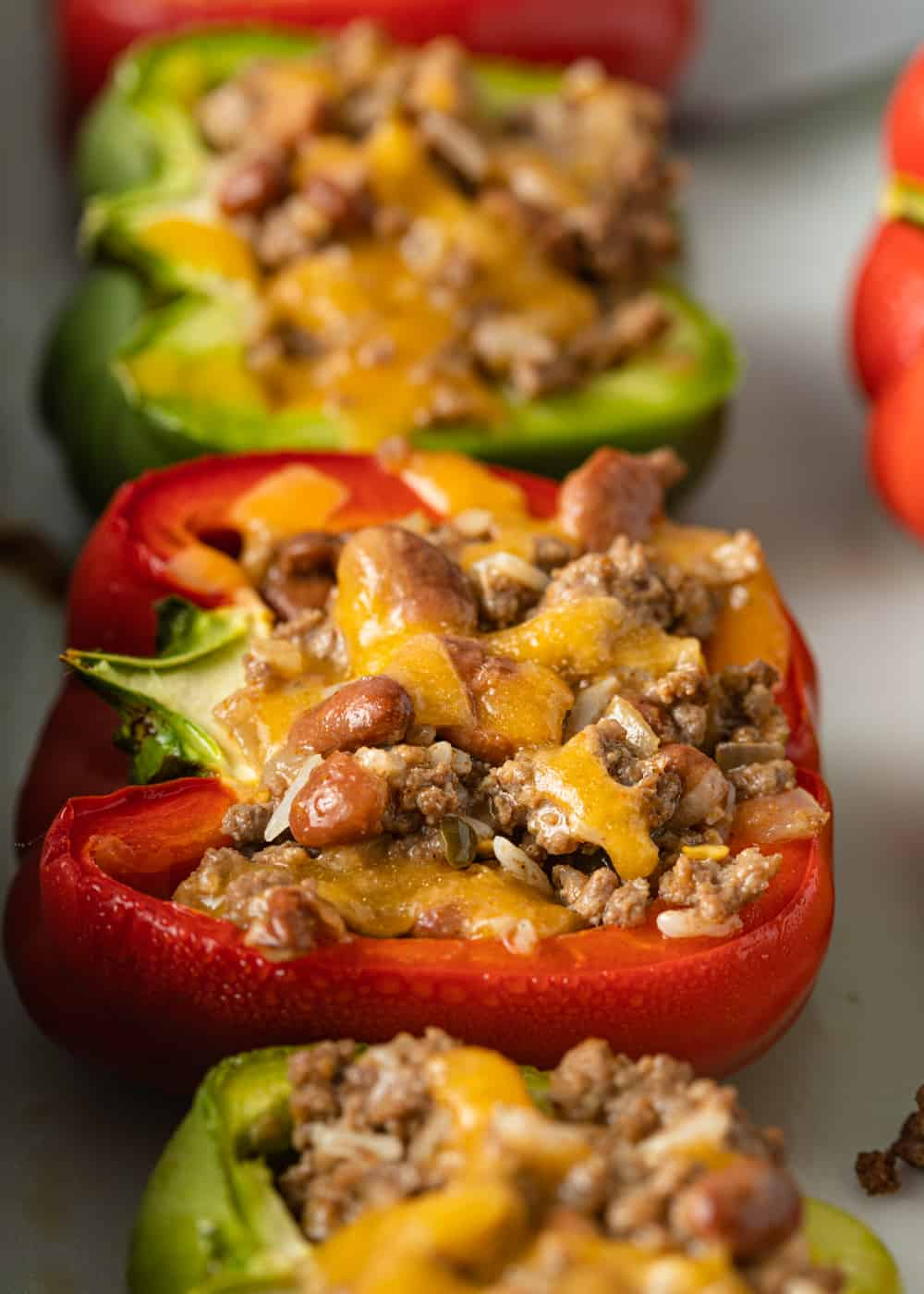 red and green bell pepper halves with filling of ground beef, beans, and cheese