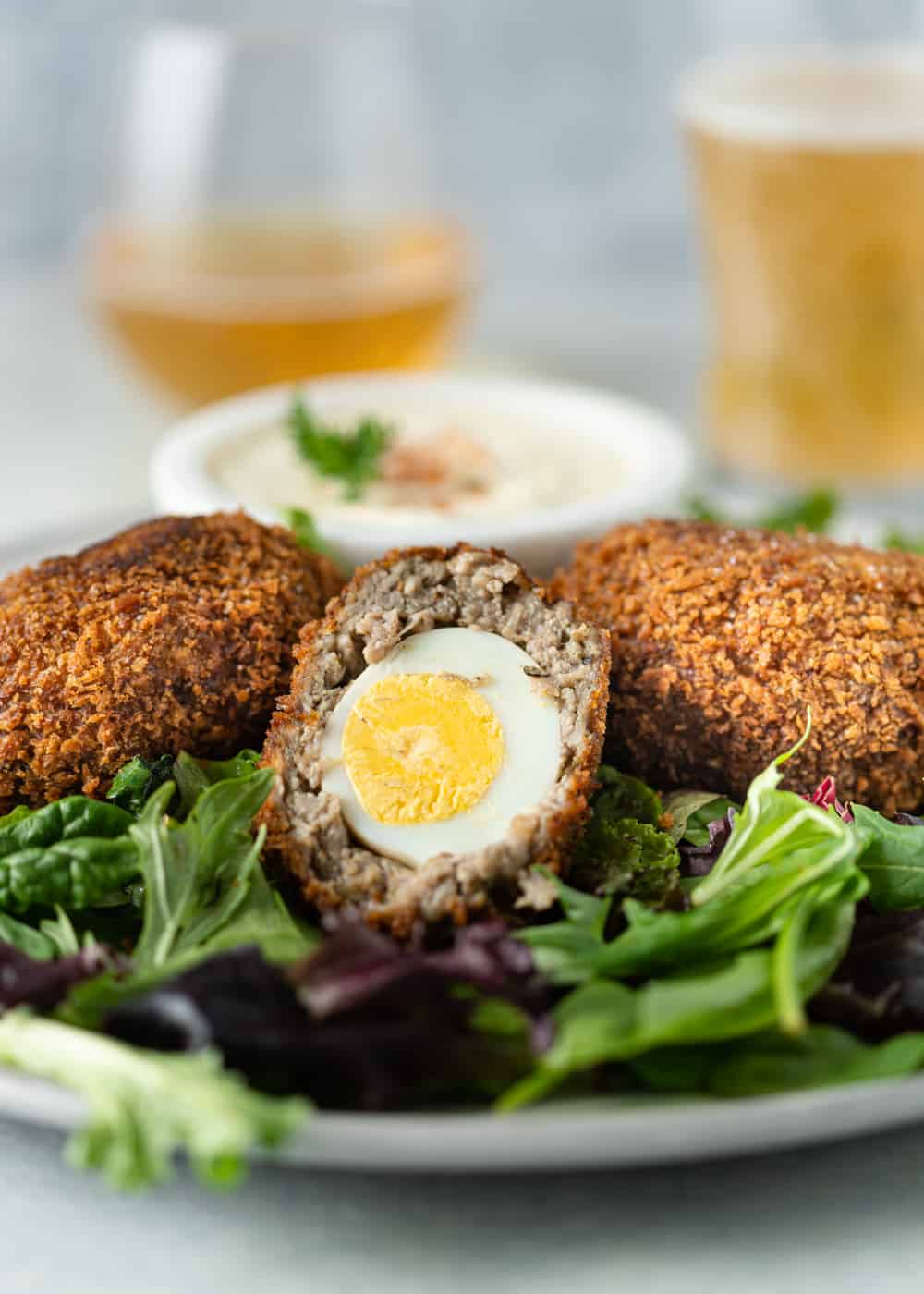 Scotch eggs on a plate with salad greens