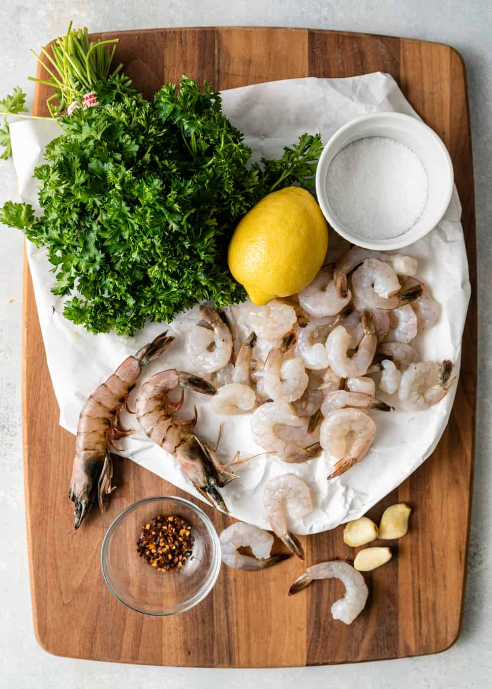 ingredients on cutting board to make shrimp scampi recipe - raw shrimp, butter, garlic, lemon, parsley