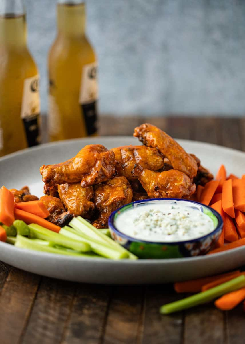 platter of buffalo wings with celery, carrots, and blue cheese dipping sauce