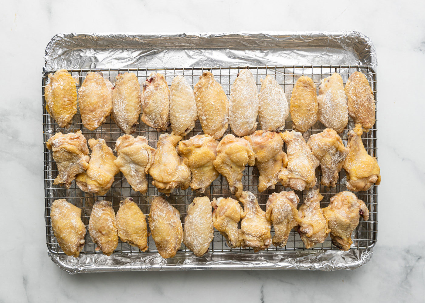 coated wings on rack in tray