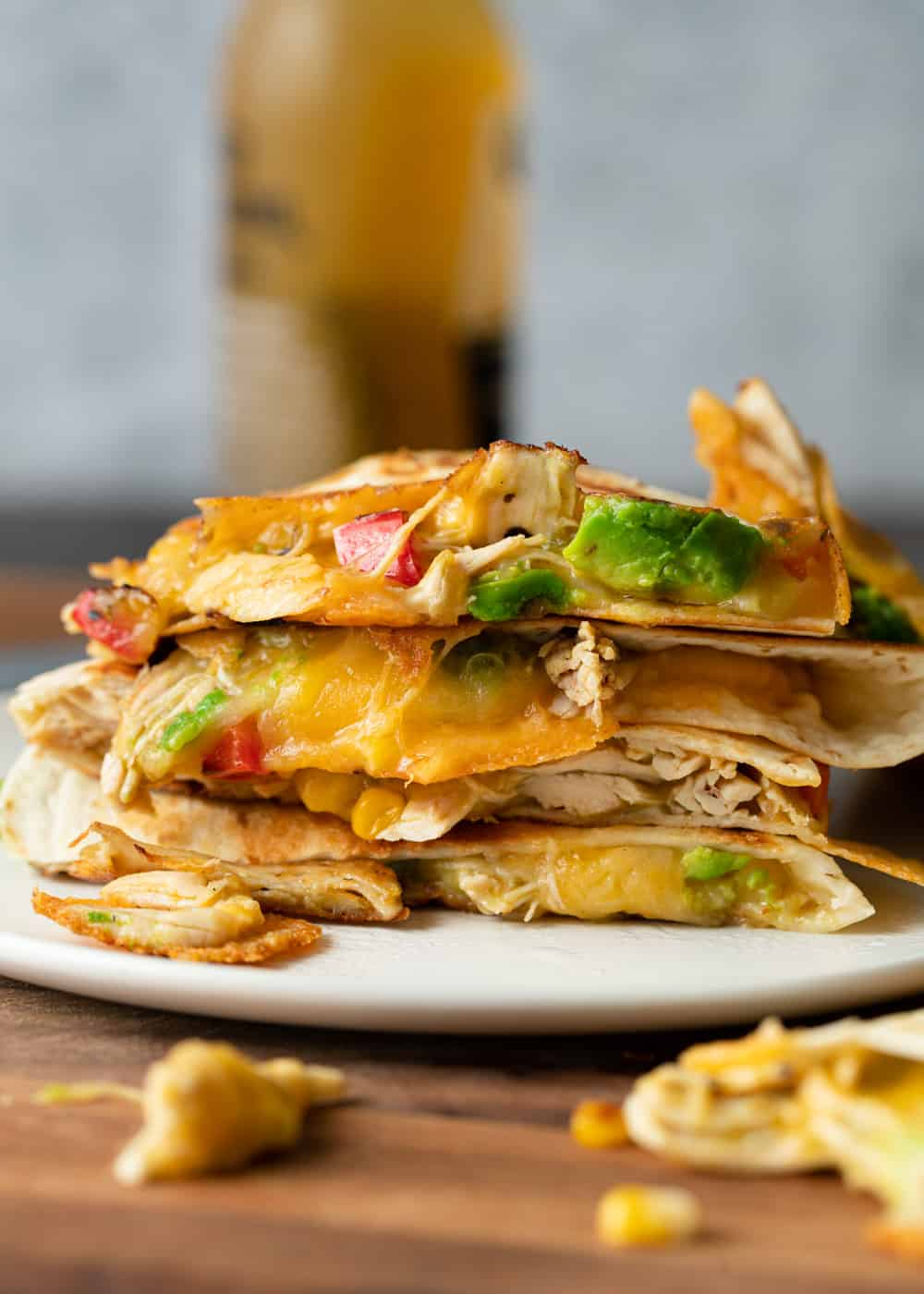 chicken quesadillas on a plate with beer in the background