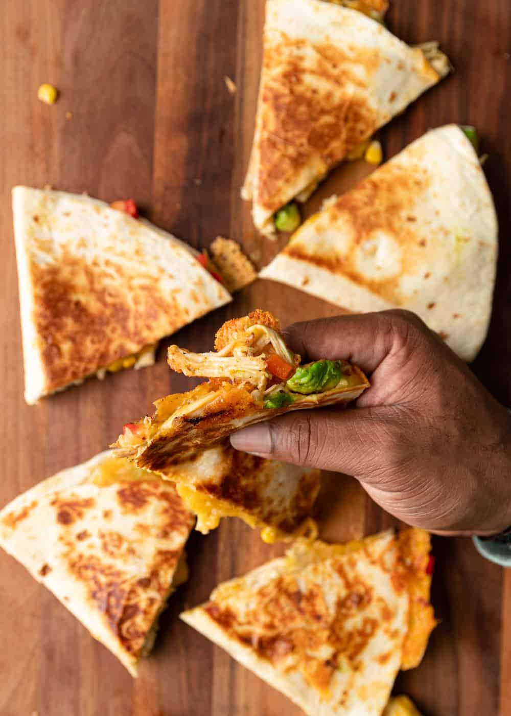 man's hand holding a quesadilla slice