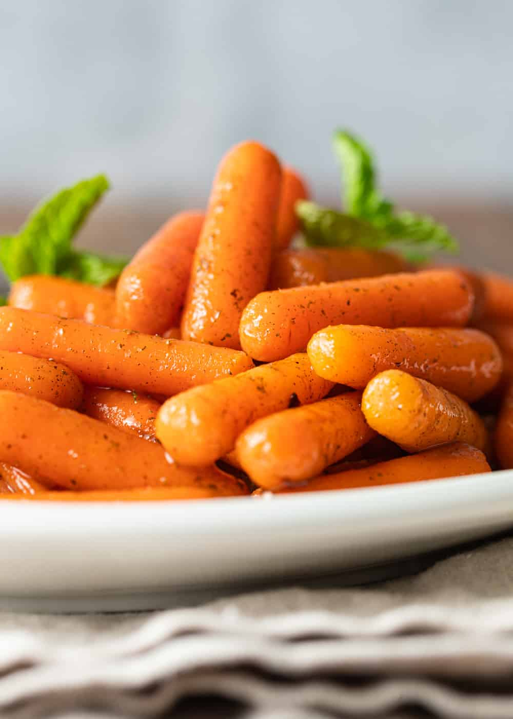 close up image of sauteed carrots on a white plate
