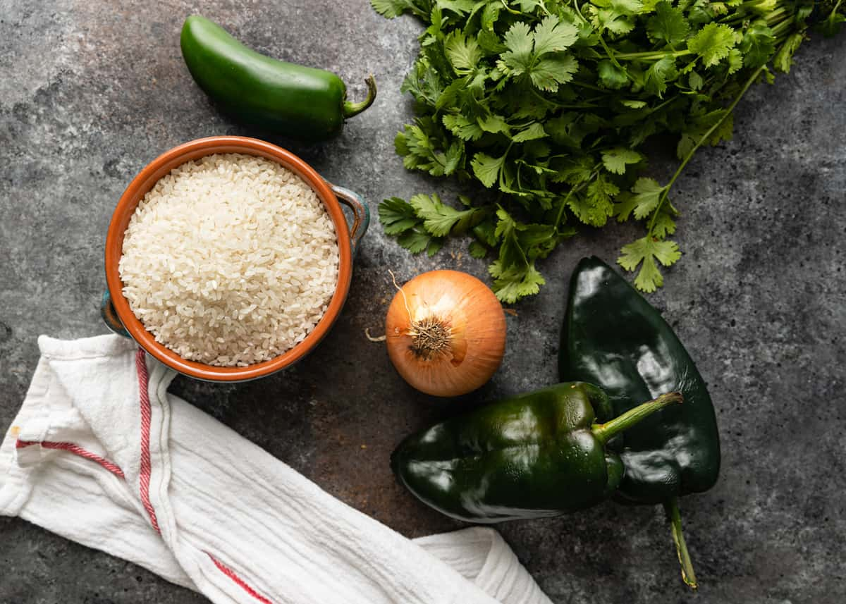 fresh green chiles, onion, cilantro and raw rice on counter top