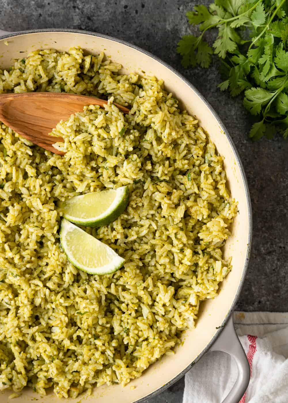 wooden spoon in a pan of Mexican rice with lime wedges