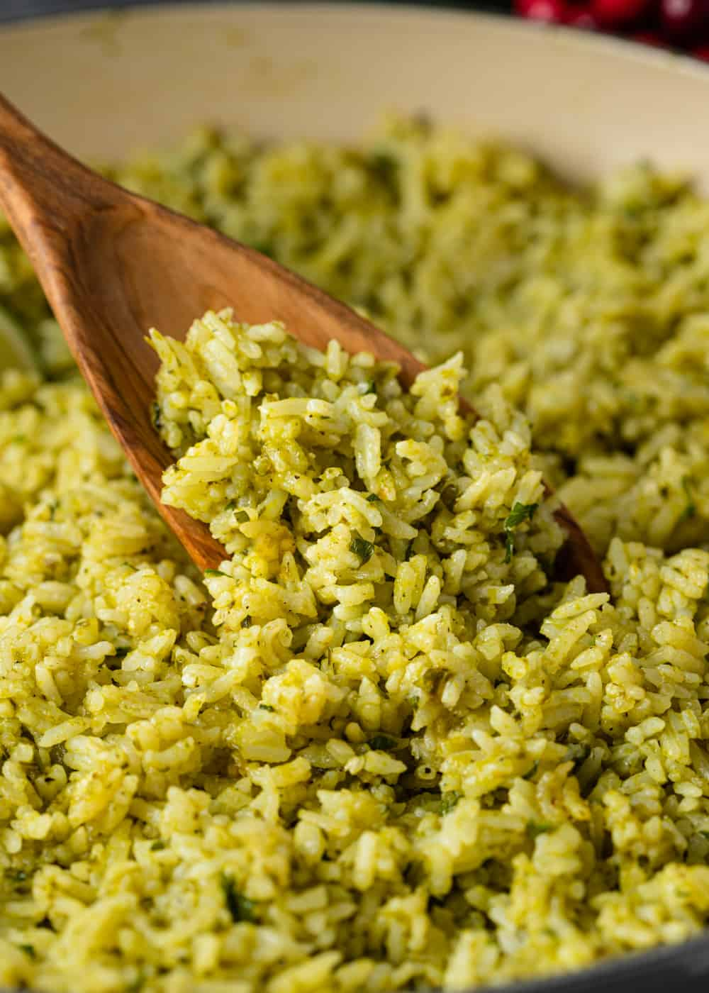 wooden spoon stirring pot of arroz verde Mexican rice