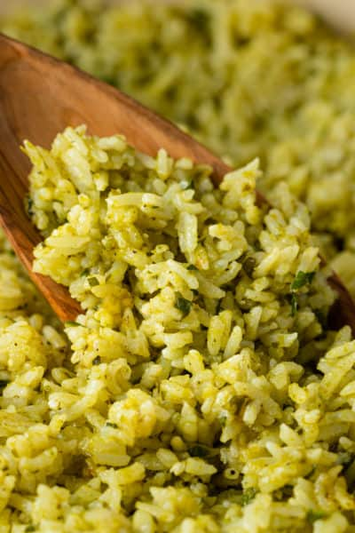 wooden spoon stirring green rice