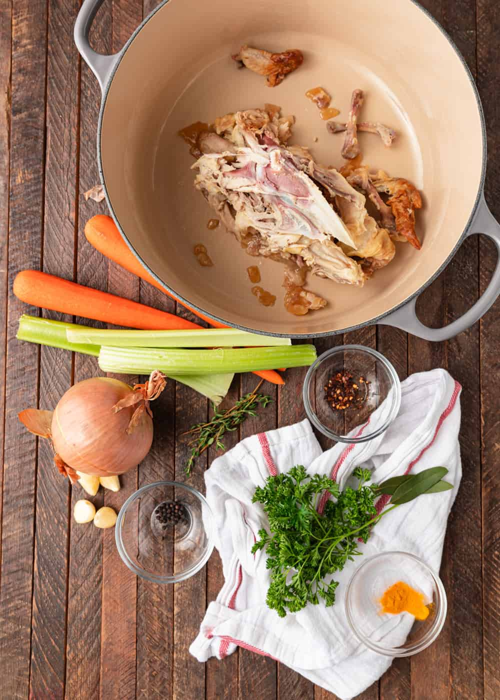 large pot with chicken carcass next to carrots, celery, onion, and herbs
