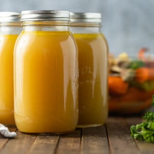A close up of Glass jars of chicken broth