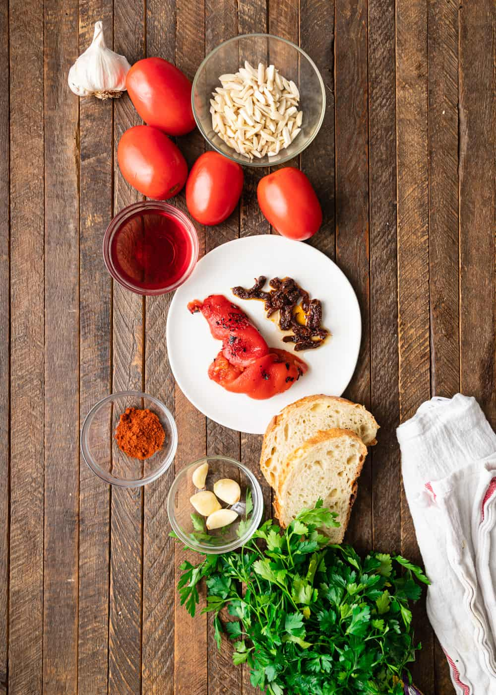 overhead photo: fresh tomatoes, garlic, pine nuts, and other ingredients to make a romesco sauce recipe laying on a wooden table