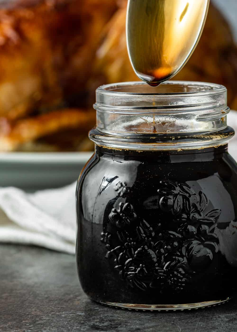 teriyaki sauce recipe dripping from spoon into a glass jar