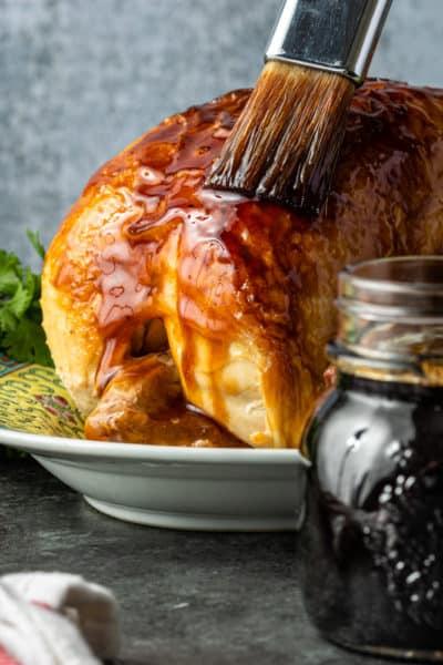 brushing teriyaki sauce onto a platter of roast chicken