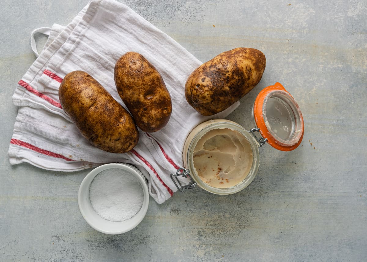 ingredients to make a baked potato recipe: potatoes, sea salt, and bacon fat