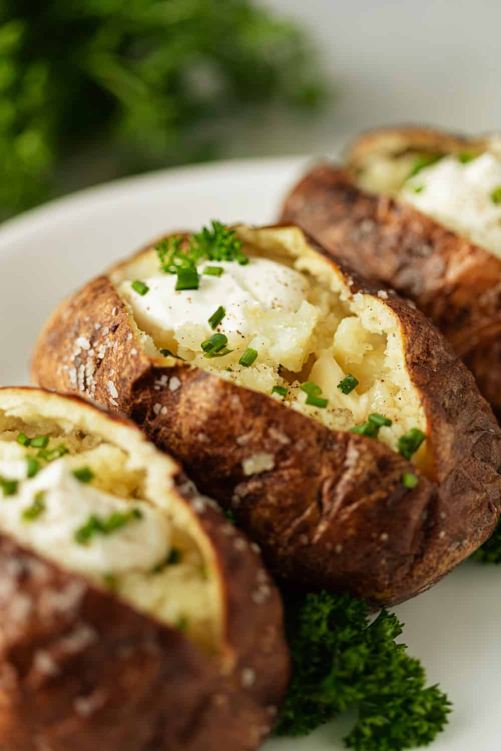 A close up of a plate of a Baked potato, sliced with sour cream and chives on top