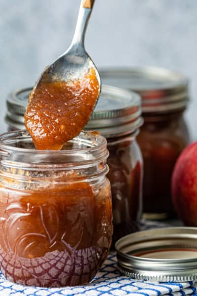 spoonful of homemade apple butter above a jar full